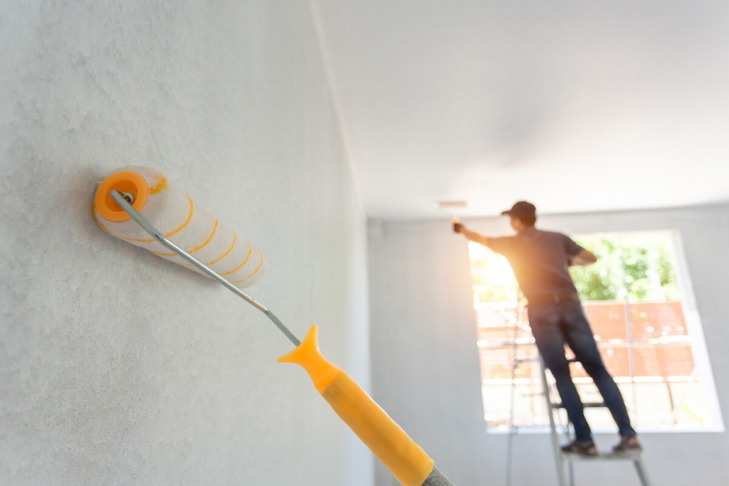 Roller painting the interior of a house